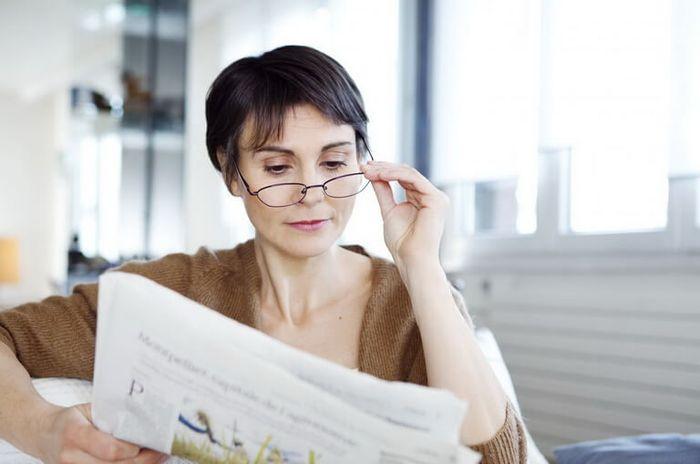 Женщина читающая газету