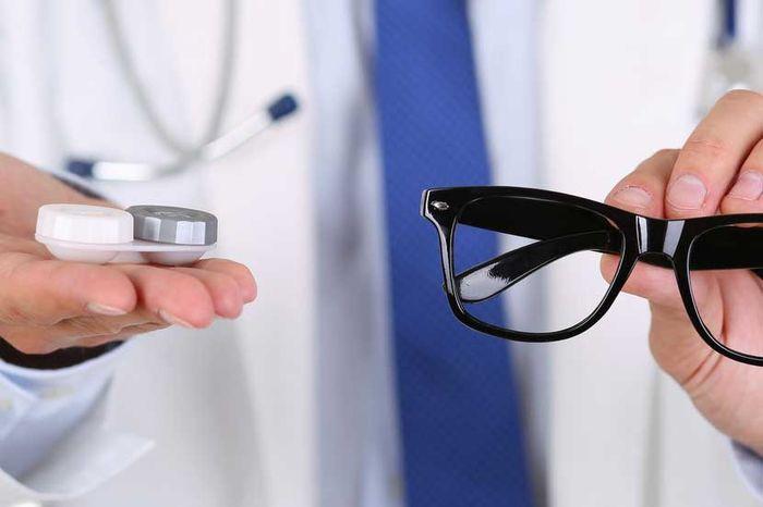 Врач с очками и линзами в руках