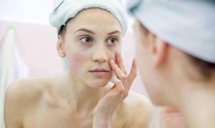 Женщина осматривающая лицо в зеркале